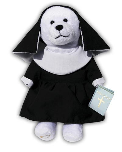 White plush bear wearing a black nun's habit and black veil. Bear is holding a blue Holy Bible.