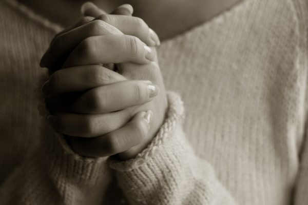 women's hands clasped in prayer.