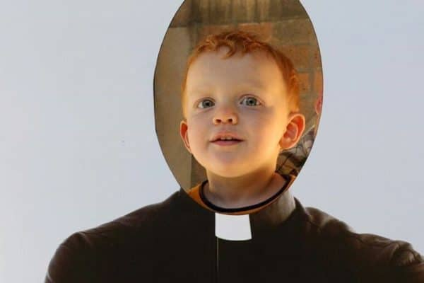 Boy looking through a priest cutout.
