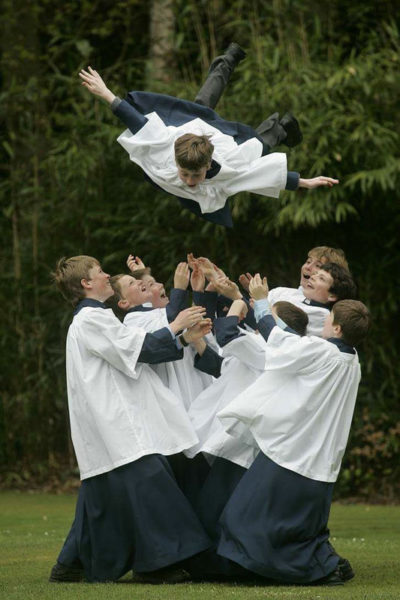young boys dressed as altar servers tossing a boy into the air.