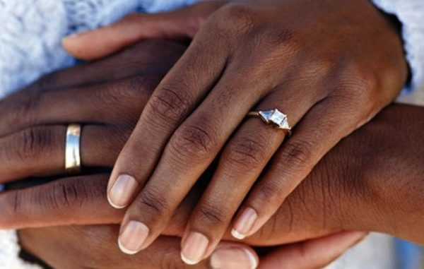 a couple's hands clasping with wedding bands visible