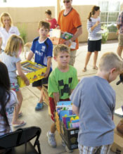 children serving others by carrying boxes.
