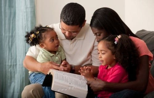 african american family reading the bible together.
