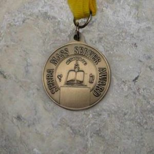 Pendant with text that says serra mass server award.