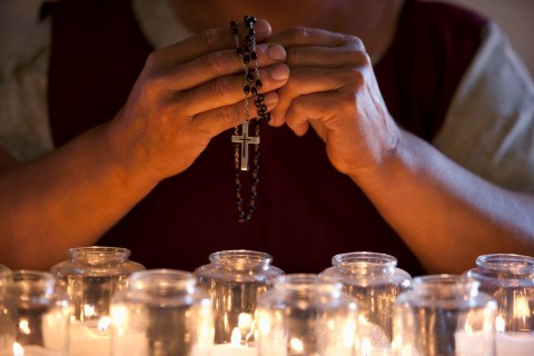 Woman's hands praying over candles with rosary.
