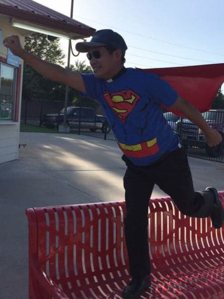 priest dresed in superman costume.