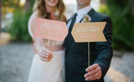 "bride and groom holding signs that say ""I'm his MRS. and I'm her MR."""