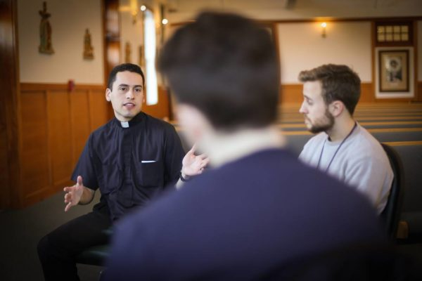 priest talking to young men.